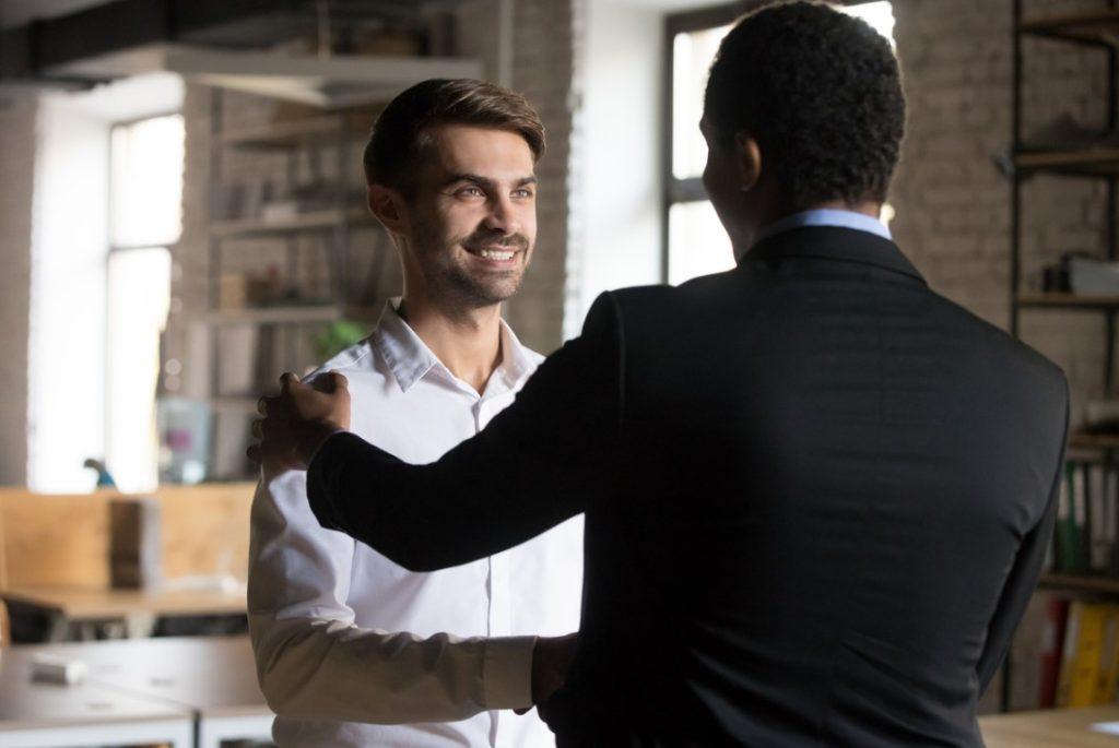 cliente em destaque com sorriso no rosto porque está sendo bem atendido pelo vendedor que o atendeu.