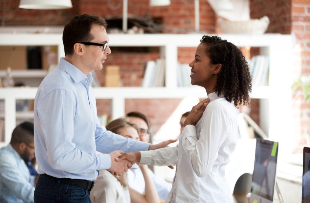 Vendedor atendendo a cliente de forma empática. Os dois estão vistos de lateral e parecem satisfeitos um com o outro