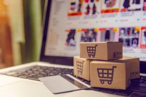 Compras on-line conceito - serviço de compras na web on-line. com pagamento por cartão de crédito e oferece entrega em domicílio. pacote ou caixas de papel com um logotipo de carrinho de compras em um teclado de laptop.