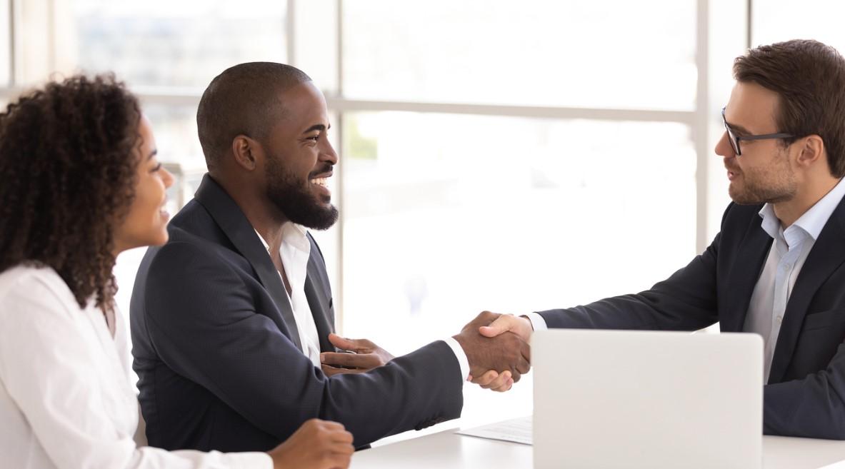 imagem de vendedor e cliente sorrindo após a venda de  um determinado produto.