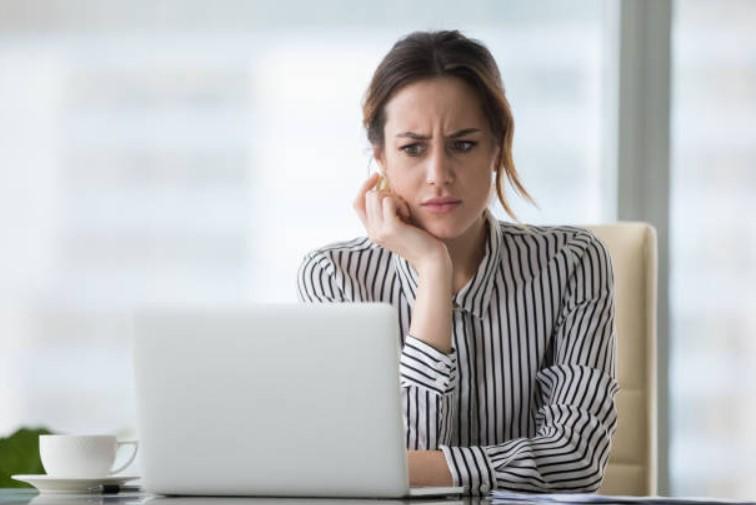 mulher parada em frente ao computador com cara de incrédula