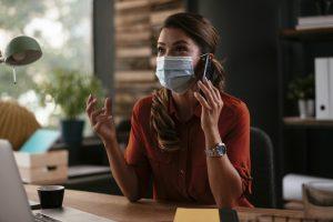Linda mulher de negócios com máscara médica, trabalhando no escritório. Jovem empresária falando ao telefone. Mudança de comportamento das pessoas.
