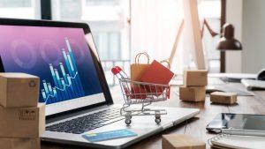 Sacos de compras no carrinho de compras e cartão de crédito no laptop com caixas de papel na mesa e gráfico de crescimento econômico de dados de vendas na tela, serviços de compra e venda online na rede, compras online e conceito de e-commerce. Tendências de inovação no setor do varejo.