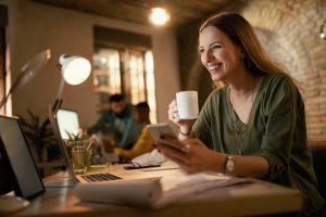 Feliz empresário usando telefone e bebendo café enquanto trabalhava até tarde em seu escritório e acompanhando pelo celular sua entrega..