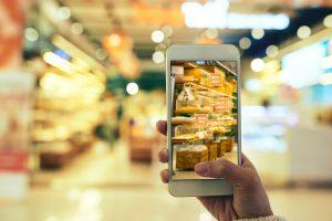 Close-up de uma mulher irreconhecível verificando as ofertas com a ajuda do aplicativo de realidade aumentada enquanto faz compras no hipermercado, fundo desfocado.