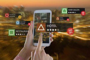 Smartphone com aplicativos em vista de alto ângulo da paisagem urbana iluminada. Cliente oculto avaliando serviços de empresas.