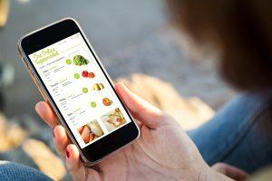 Vista do close-up de jovem mulher fazendo compras no supermercado online com seu telefone celular. Todos os gráficos da tela são compostos.